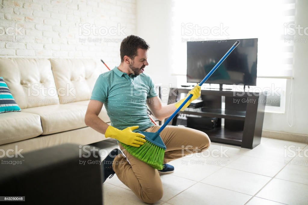 Attractive man using broom as a guitar stock photo