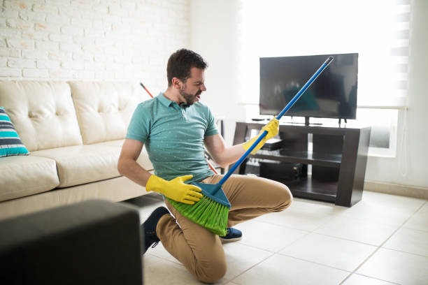 Attractive man using broom as a guitar Playful man in the living room having fun while doing house chores and holding a broom as a guitar broom stock pictures, royalty-free photos & images