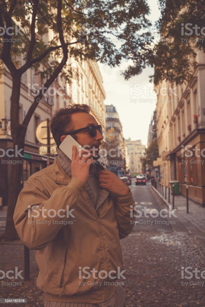 Attractive man using cellphone in the European city. stock photo