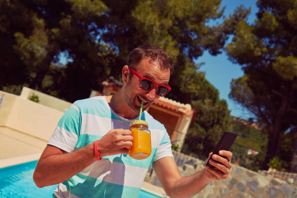 Attractive man using cellphone while drinking juice near swimming pool. stock photo