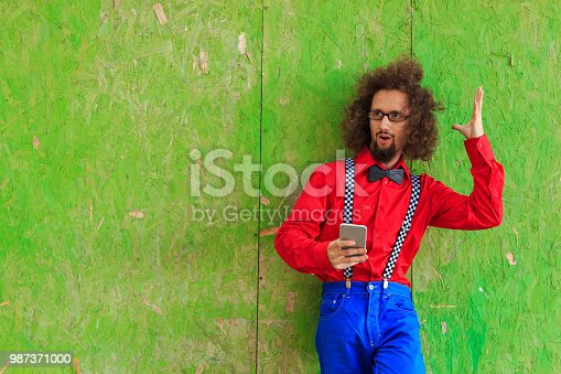 Attractive man using smart phone on a green background