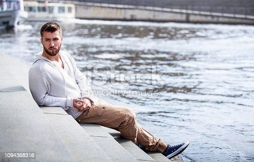 Attractive man with a beard is sitting on steps