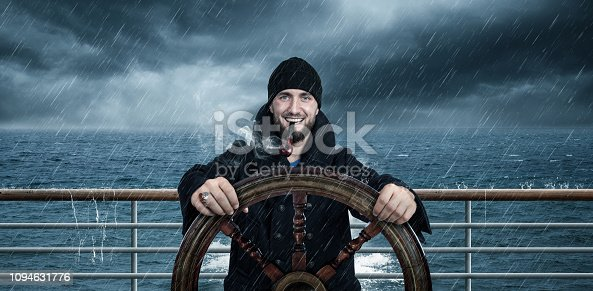 istock Attractive man with beard is driving the ship through rough seas 1094631776