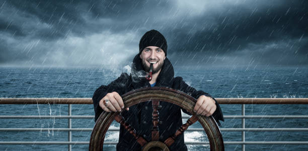 Attractive man with beard is driving the ship through rough seas Attractive man with beard is driving the ship through rough seas sailor stock pictures, royalty-free photos & images