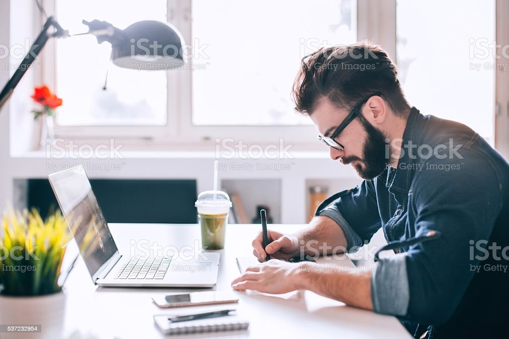 Attractive man working at modern office space stock photo