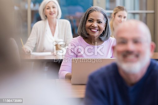 istock Attractive mature adult woman smiles and listens to unrecognizable teacher 1156473589