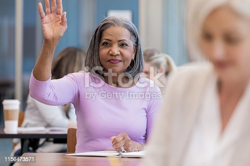 An attractive mature African American woman asks a question by raising her hand in class.