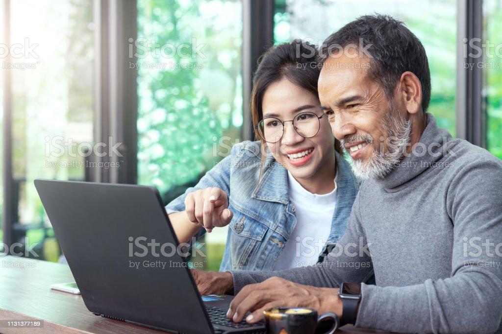 魅力的な成熟しましたアジアの男とともにホワイトスタイリッシュ短い髭を見てラップトップコンピュータで10代目メガネヒップスター女性カフェ.古い男のコンセプトでインターネットオン� - 2人のロイヤリティフリーストックフォト