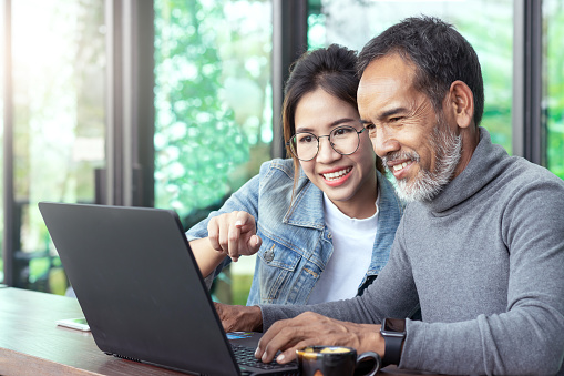 Attractive Mature Asian Man With White Stylish Short Beard Looking At Laptop Computer With Teenage Eye Glasses Hipster Woman In Cafe Teaching Internet Online Or Wifi Technology In Older Man Concept Stock Photo - Download Image Now