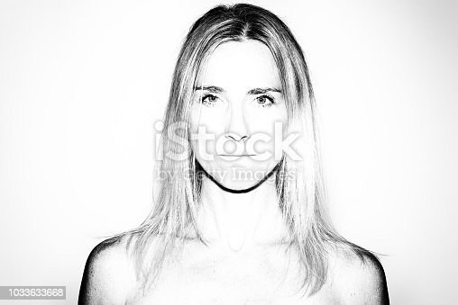 Attractive mature blond woman with bare shoulders staring at the camera with a serious unemotional expression in black an white