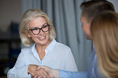 Attractive mature businesswoman in glasses with sincere smile make eye contact shaking hands greeting business associate showing amity support and respect starting business meeting with polite gesture