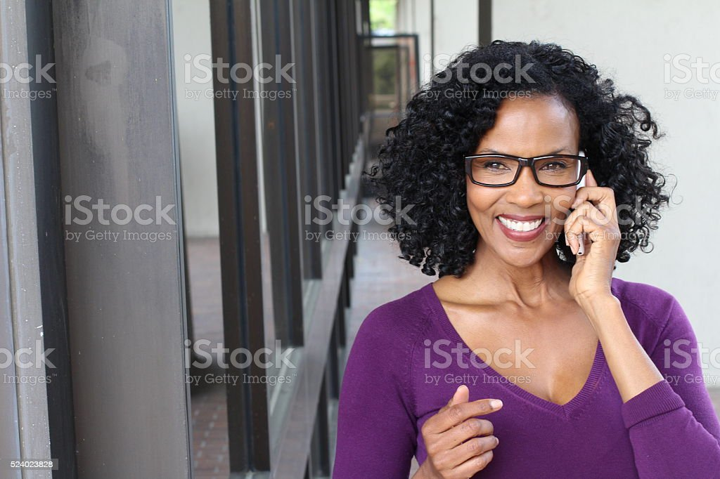Attractive mature business woman with smart phone stock photo