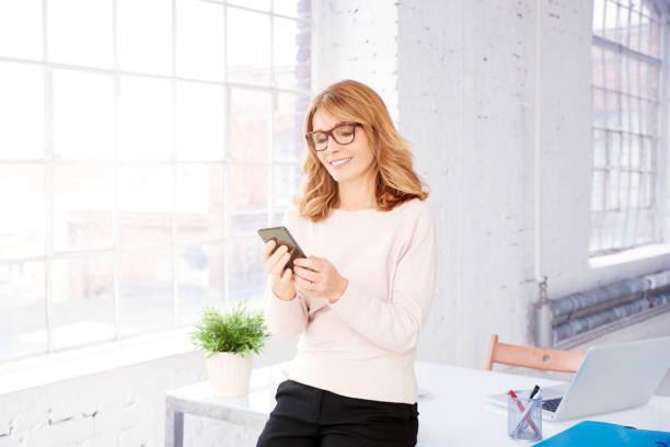 Attraktive, reife Geschäftsfrau mit ihrem Handy und SMS – Foto