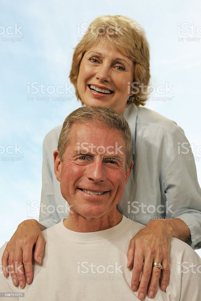 Attractive mature couple in their fifties woman behind a man royalty-free stock photo