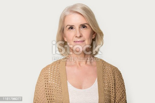 istock Attractive mature woman looking at camera isolated on grey background 1151796077