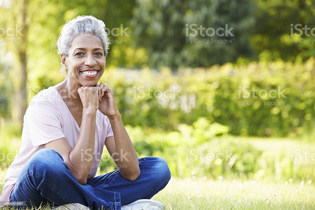 Attractive Mature Woman Sitting In Garden stock photo