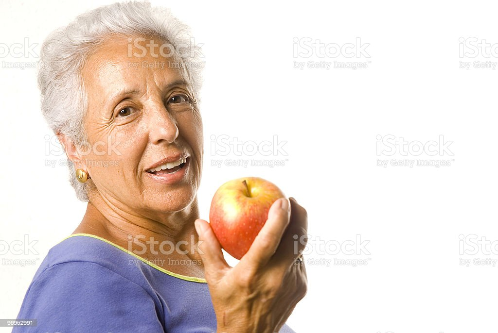 Attractive mature woman with an apple royalty-free stock photo