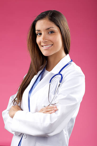 Attractive medical professional on bright background stock photo
