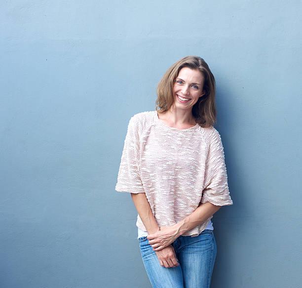 atractiva mujer de mediana edad sonriendo sobre fondo gris - mujeres de mediana edad fotografías e imágenes de stock