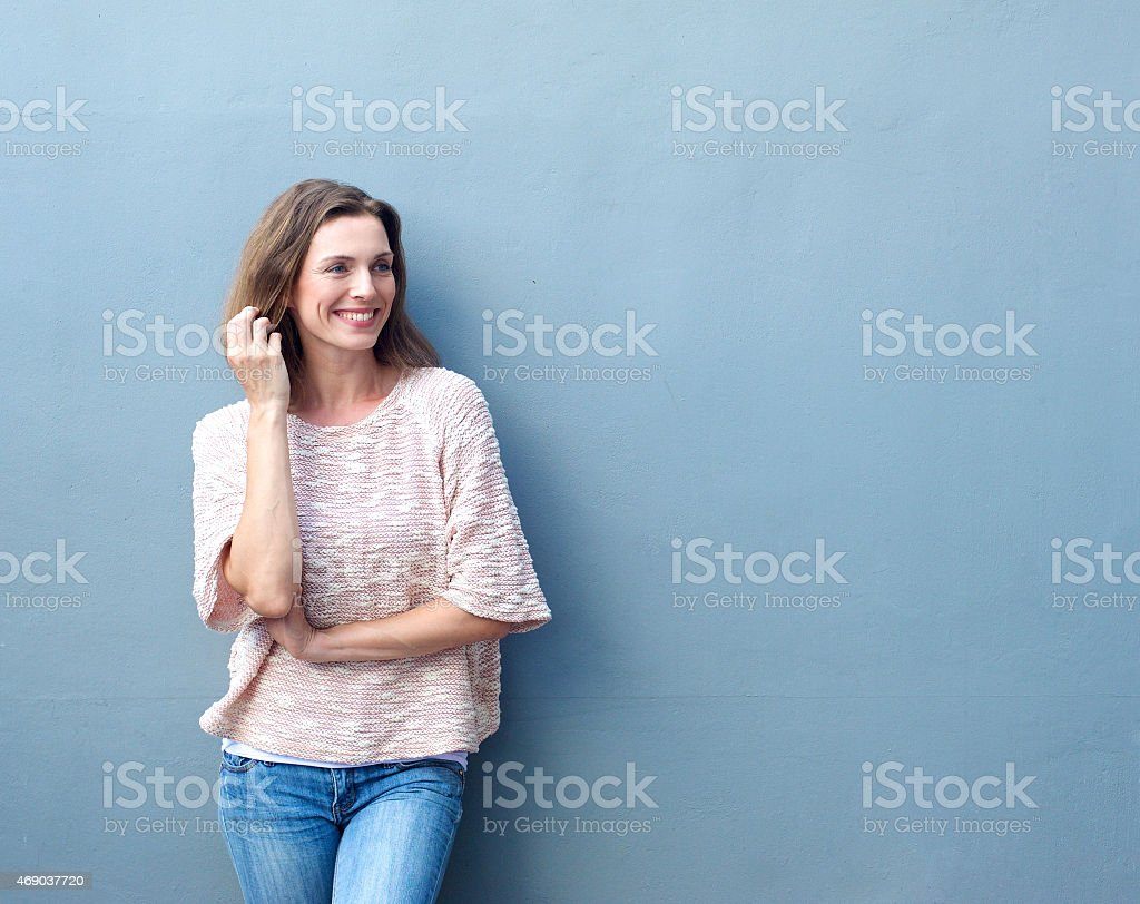 Attractive mid adult woman smiling with hand in hair stock photo