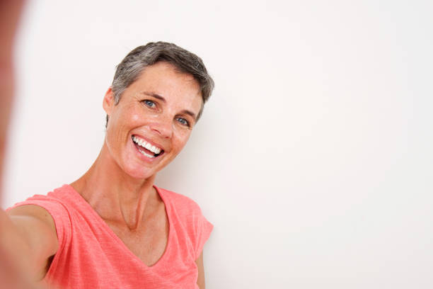 attractive middle age woman smiling and taking selfie - self portrait photography stock pictures, royalty-free photos & images