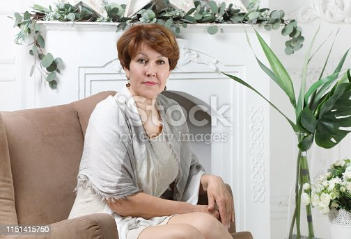 Portrait of an attractive middle aged woman sitting in a chair by the fireplace in the living room bathed in sunlight