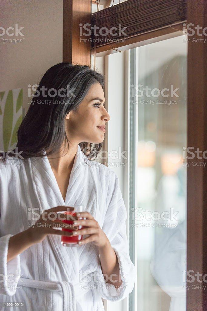 Attraente mediorientale donna in accappatoio nella Spa con bicchiere di succo di frutta - foto stock