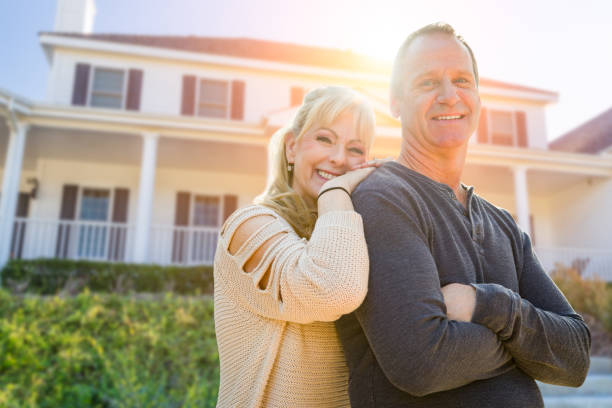 attractive middle-aged couple in front of their house - vendere foto e immagini stock