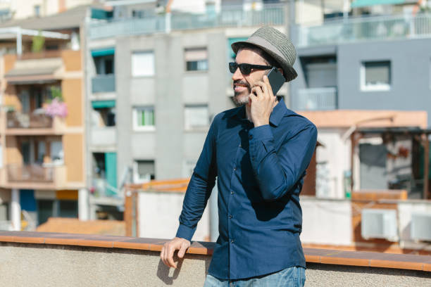 Attractive middle-aged man with hat and sunglasses talking to a smart phone standing on balcony. stock photo