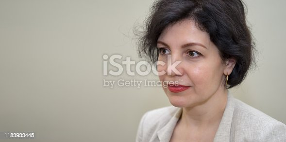 981750034 istock photo Attractive middle-aged successful women with beautiful smile in business suit against concrete beige wall, head and shoulders portrait with copy space. 1183933445