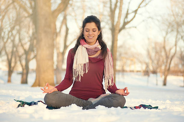 Attractive mixed race woman doing yoga in nature at winter stock photo