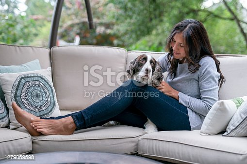 A beautiful Eurasian woman sits on patio furniture in her home's backyard and cuddles her pet dog. Pet adoption and emotional support mental health animal concepts.