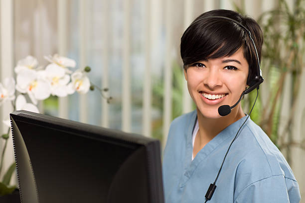 attractive multi-ethnic young woman wearing headset and scrubs - nurse on phone stock photos and pictures