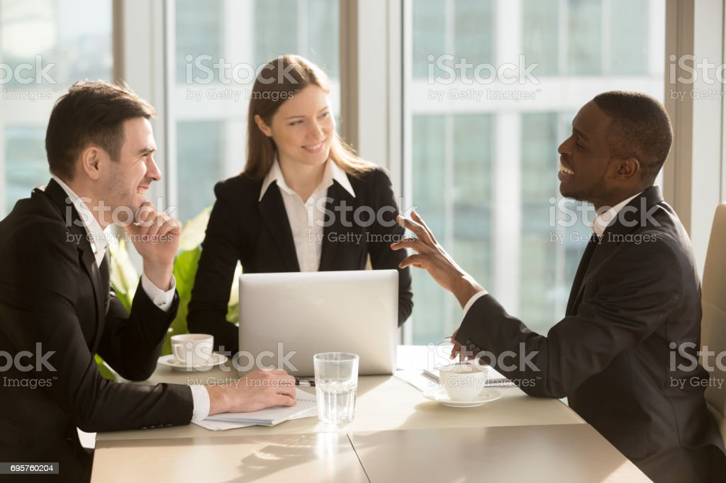 Attractive multiracial businesspeople talking and joking, having fun at meeting stock photo