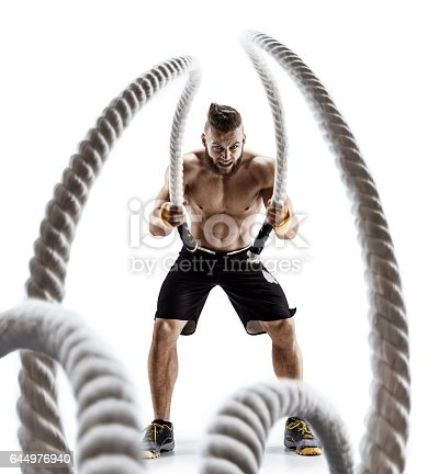 istock Attractive muscular man working out with heavy ropes. 644976940