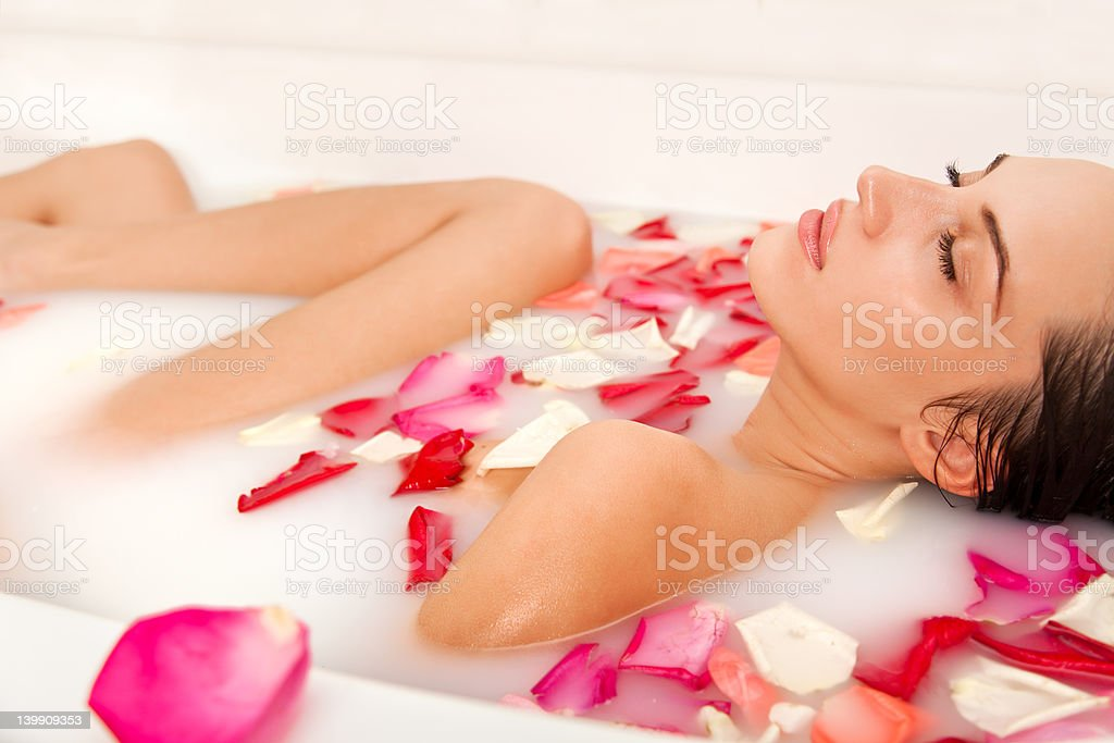 Attractive naked girl enjoys a bath with milk and petals stock photo