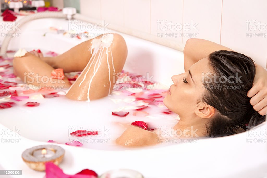 Attractive naked girl enjoys a bath with milk and roses stock photo