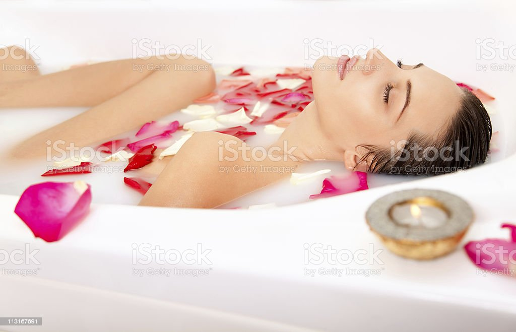 Attractive naked girl enjoys a milk bath with rose petals royalty-free stock photo