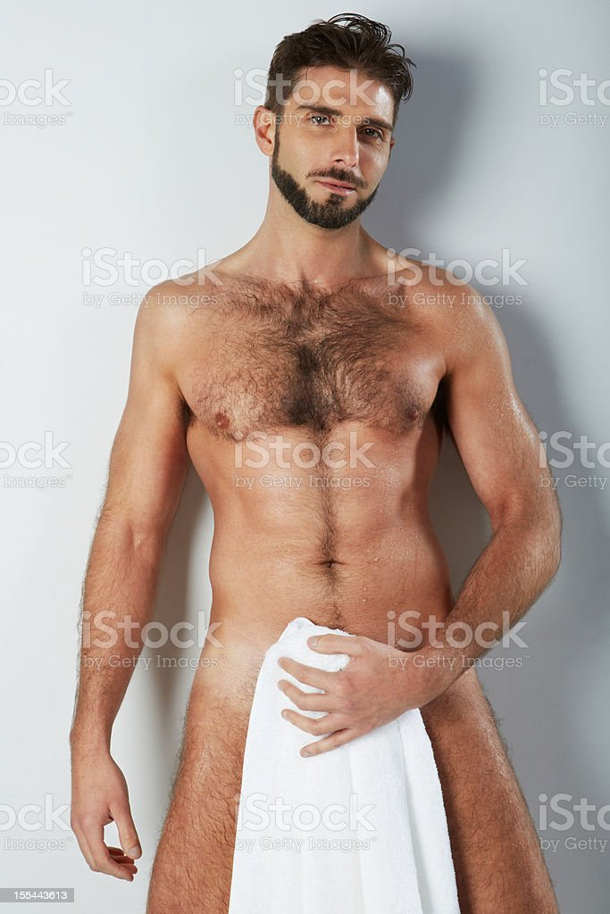 Attractive naked hairy man holding bath towel covering smiling stock photo