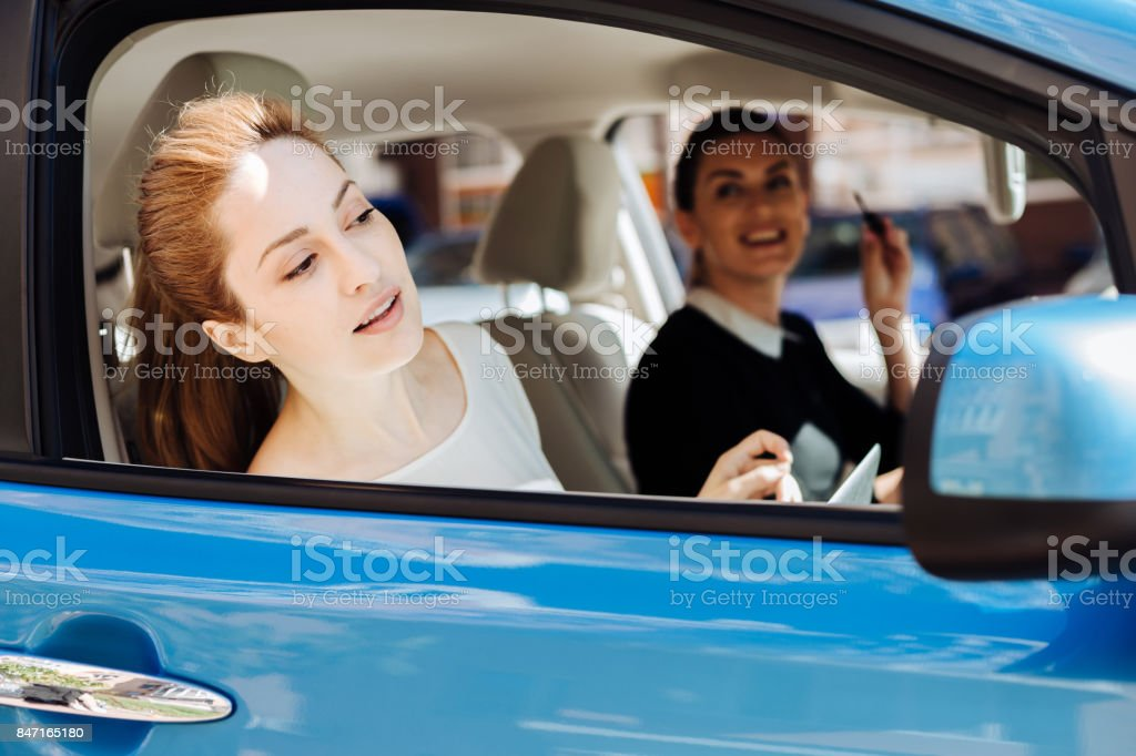 Attractive nice businesswoman sitting in the car with her colleague stock photo