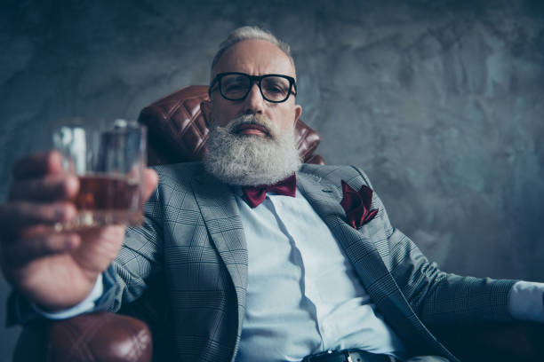 Attractive, old investor in spectacles, hold glass with brandy, in tuxedo with red bowtie and pocket square, sit in leather chair over gray background, looking at the camera, shares, stock, money - foto stock