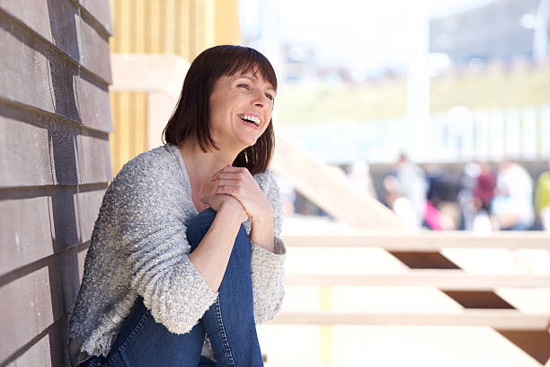 Attractive older woman laughing outdoors Portrait of an attractive older woman laughing outdoors one mid adult woman only stock pictures, royalty-free photos & images