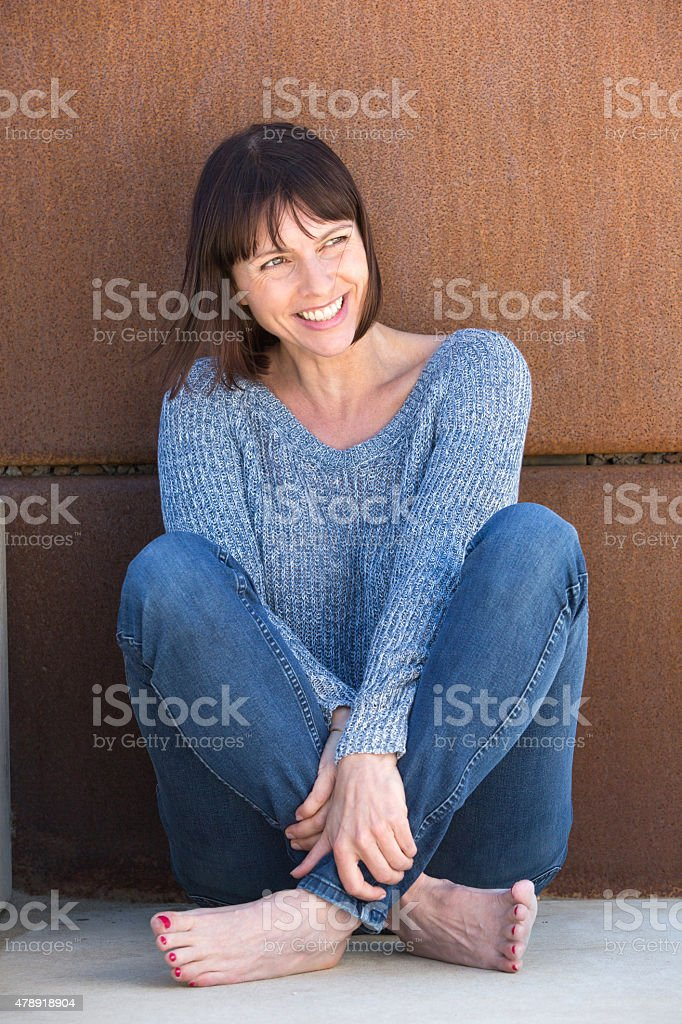 Attractive older woman sitting and smiling stock photo