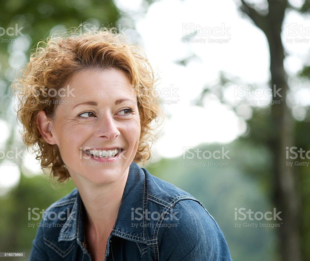 Attractive older woman smiling and looking away stock photo