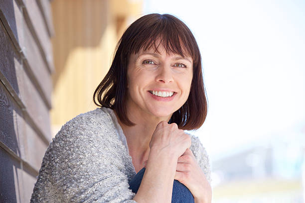 Attractive older woman smiling Close up portrait of an attractive older woman smiling one mature woman only stock pictures, royalty-free photos & images