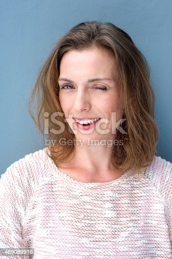 928358584 istock photo Attractive older woman winking and flirting 469089916