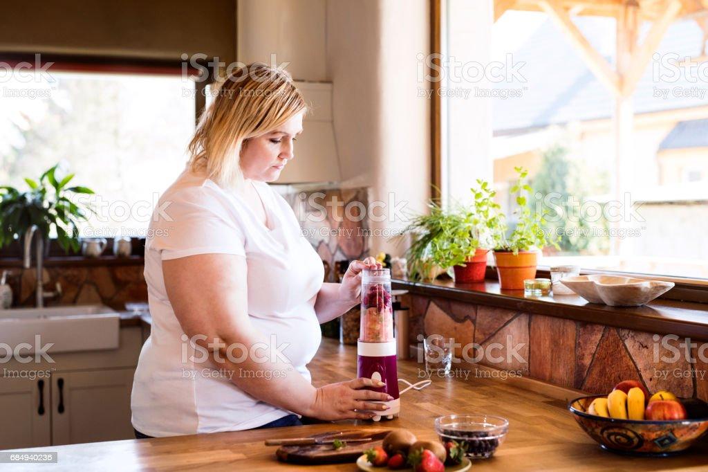 Attraktive übergewichtige blonde Frau in weißem T-shirt zu Hause vorbereiten einen köstliche gesunden Smoothie in ihrer Küche. Lizenzfreies stock-foto