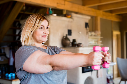 Attractive overweight woman at home holding dumbbells, working out.