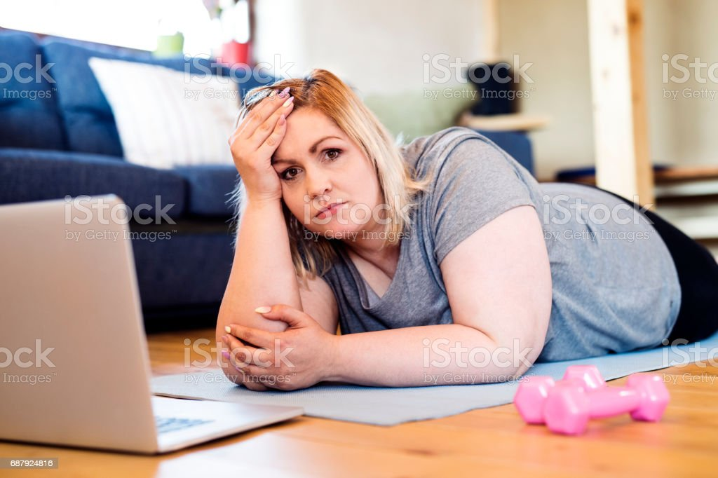 Attractive overweight woman at home lying on the floor, laptop in front of her, prepared to work out on mat according to video