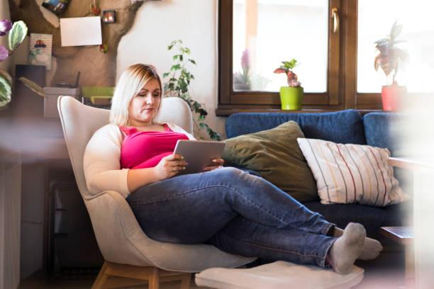 attraktive übergewichtige frau zu hause sitzen im sessel arbeiten auf tablet. - damen jeans übergrößen stock-fotos und bilder